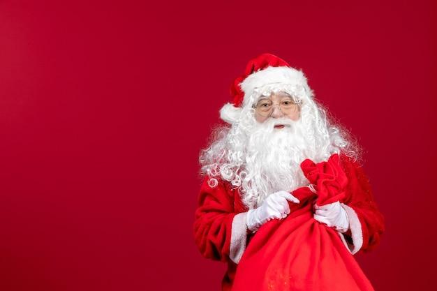 Vue de face du père noël avec un sac rouge plein de cadeaux sur un bureau rouge vacances du nouvel an émotion de noël