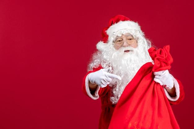 Vue de face du père noël avec un sac rouge plein de cadeaux sur la couleur rouge de l'émotion de noël des vacances du nouvel an