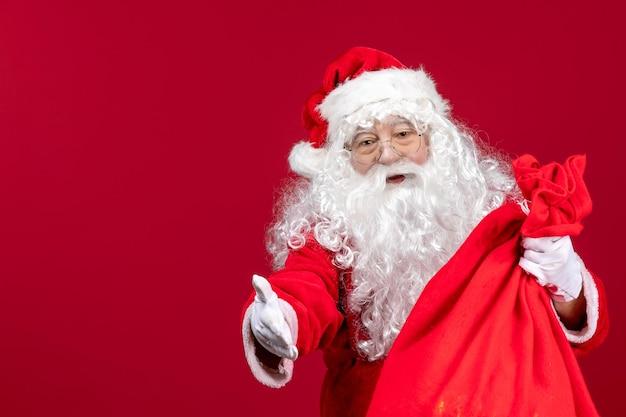 Vue de face du père noël avec un sac rouge plein de cadeaux sur l'émotion de noël des vacances du nouvel an rouge