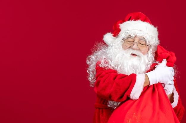 Vue de face du père noël avec un sac rouge plein de cadeaux pour les enfants sur un bureau rouge nouvel an