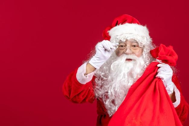 Vue de face du père noël avec un sac rouge plein de cadeaux pour les enfants sur l'émotion de noël des vacances du nouvel an rouge