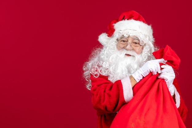 Vue de face du père noël avec un sac rouge plein de cadeaux pour les enfants le nouvel an rouge