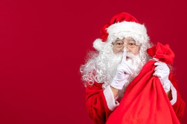 Vue de face du père noël avec un sac rouge plein de cadeaux pour les enfants sur le rouge