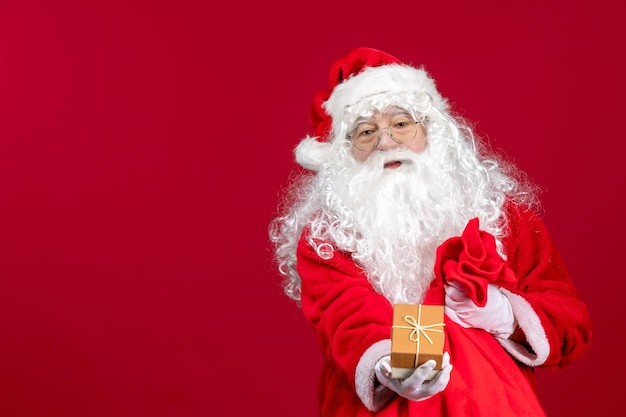 Vue de face du père noël tenant un cadeau d'un sac plein de cadeaux pour les enfants sur un bureau rouge
