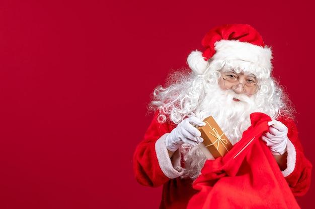 Vue de face du père noël tenant un cadeau d'un sac plein de cadeaux pour les enfants sur les émotions rouges du nouvel an