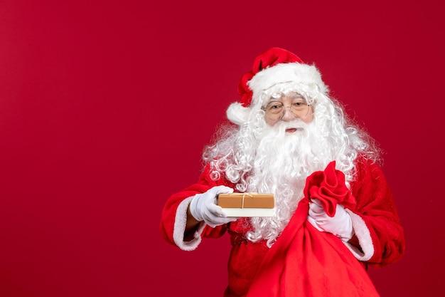 Vue de face du père noël tenant un cadeau d'un sac plein de cadeaux pour les enfants le jour de l'émotion rouge du nouvel an