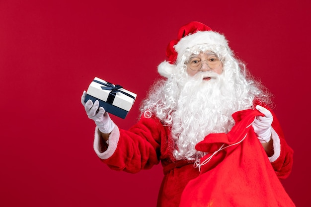 Vue de face du père noël tenant un cadeau d'un sac plein de cadeaux pour les enfants le noël du nouvel an rouge