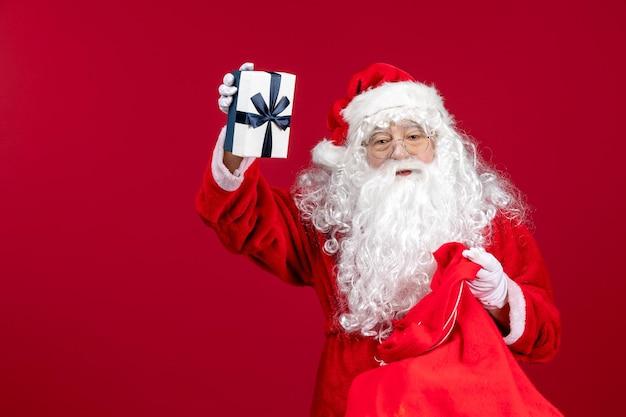 Vue de face du père noël tenant le cadeau d'un sac plein de cadeaux pour les enfants le noël du nouvel an rouge