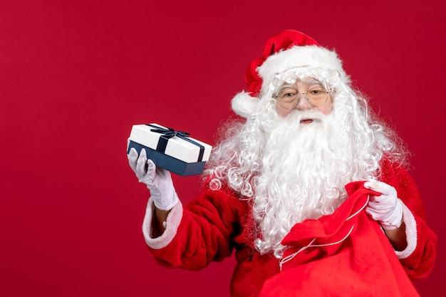 Vue de face du père noël tenant un cadeau d'un sac plein de cadeaux pour les enfants sur le sol rouge nouvel an