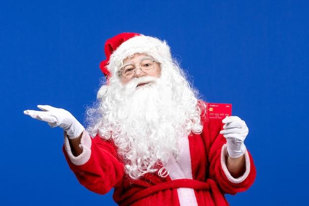 Vue de face du père noël tenant une carte bancaire rouge sur le cadeau de noël de couleur bleu nouvel an