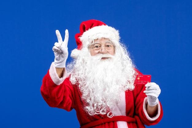 Vue de face du père noël tenant une carte bancaire rouge sur des cadeaux de noël de couleur bleu nouvel an