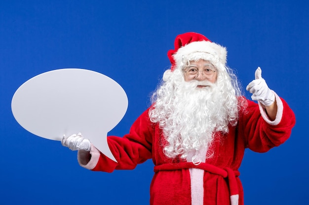 Vue de face du père noël tenant une grande pancarte blanche sur un bureau bleu couleur neige noël vacances
