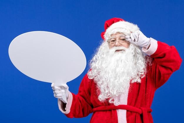 Vue de face du père noël tenant une grande pancarte blanche sur la couleur bleue des vacances de neige noël