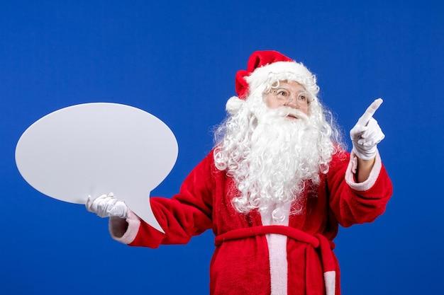 Vue de face du père noël tenant une grande pancarte blanche sur le sol bleu couleur neige vacances noël