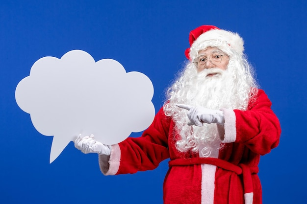 Vue de face du père noël tenant une grande pancarte en forme de nuage blanc sur un bureau bleu couleur neige noël vacances