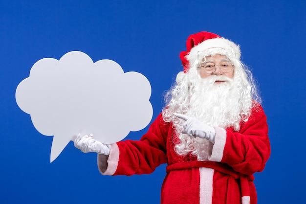 Vue de face du père noël tenant une grande pancarte en forme de nuage blanc sur la couleur bleue des vacances de neige noël