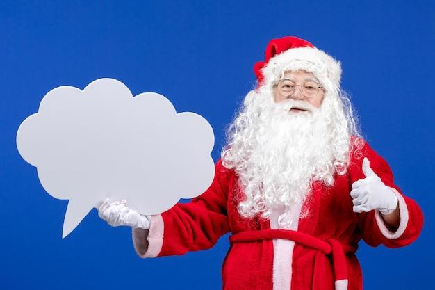 Vue de face du père noël tenant une grande pancarte en forme de nuage blanc sur un sol bleu couleur neige vacances noël