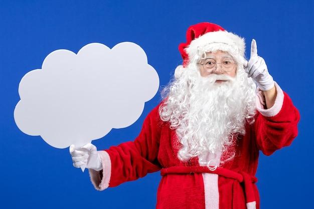 Vue de face du père noël tenant une grande pancarte en forme de nuage sur un bureau bleu couleur neige noël