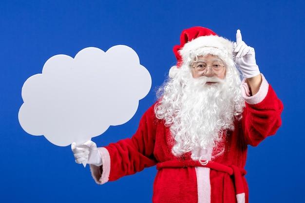 Vue de face du père noël tenant une grande pancarte en forme de nuage sur un sol bleu couleur neige noël
