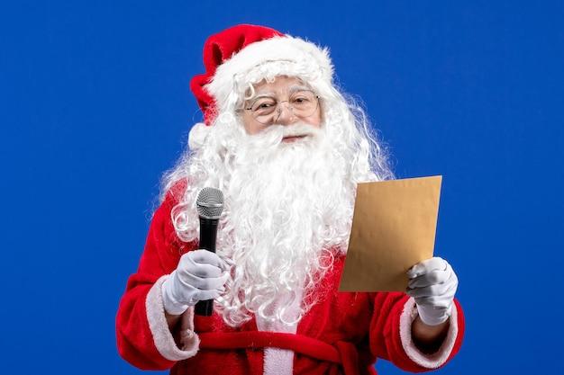 Vue de face du père noël tenant un micro et lisant une lettre sur un bureau bleu nouvelle année couleur vacances noël neige
