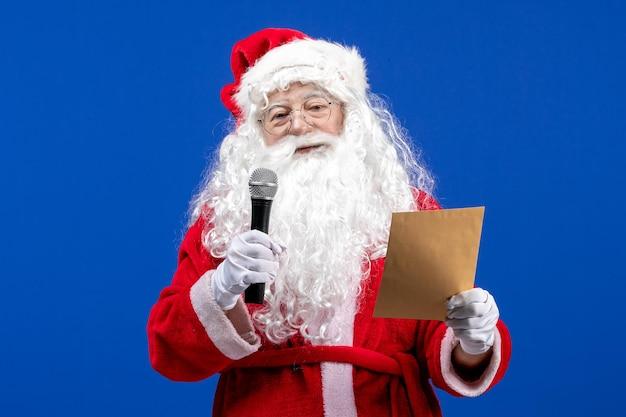 Vue de face du père noël tenant un micro et lisant une lettre sur la neige de noël de couleur bleu nouvel an