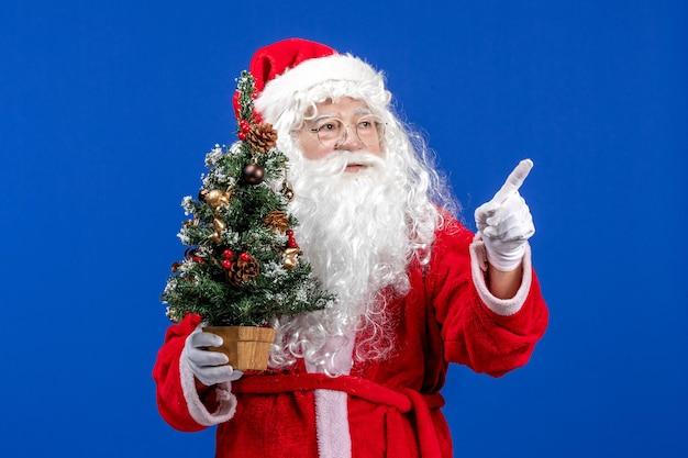 Vue de face du père noël tenant un petit arbre du nouvel an sur un bureau bleu couleur neige noël