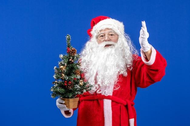 Vue de face du père noël tenant un petit arbre du nouvel an sur la neige bleue couleur de noël du nouvel an