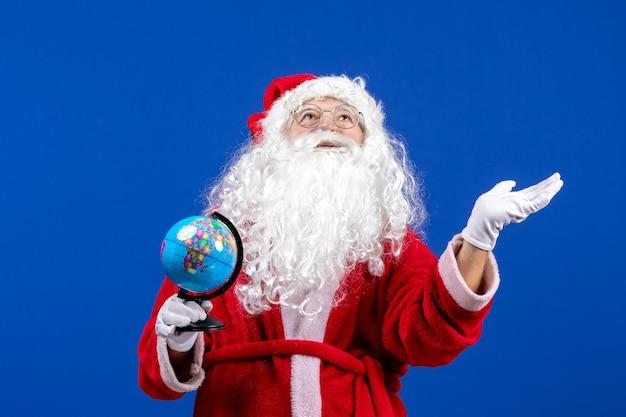Vue de face du père noël tenant un petit globe terrestre sur la couleur bleue des vacances de noël nouvel an