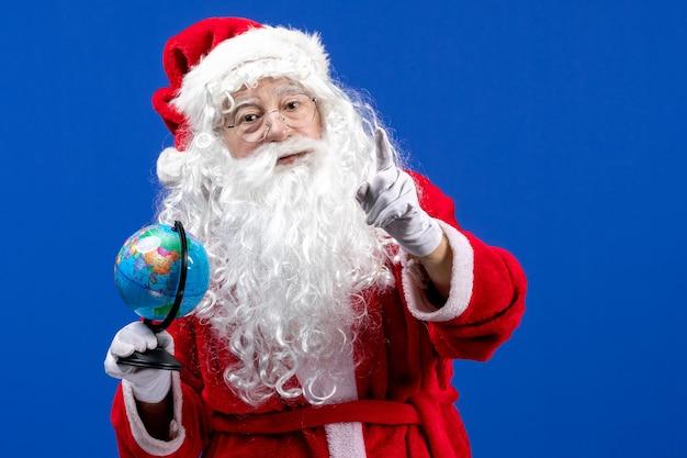 Vue de face du père noël tenant un petit globe terrestre sur un noël de vacances de couleur bleu nouvel an