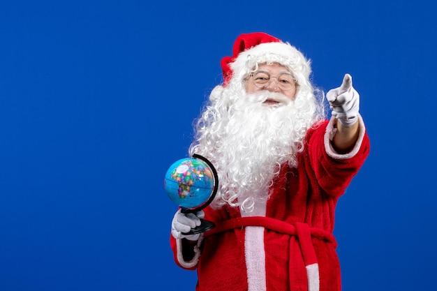 Vue de face du père noël tenant un petit globe terrestre sur le sol bleu couleur des vacances de noël nouvel an