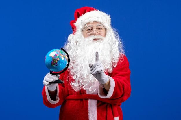 Vue de face du père noël tenant un petit globe terrestre sur les vacances de couleur bleu nouvel an noël