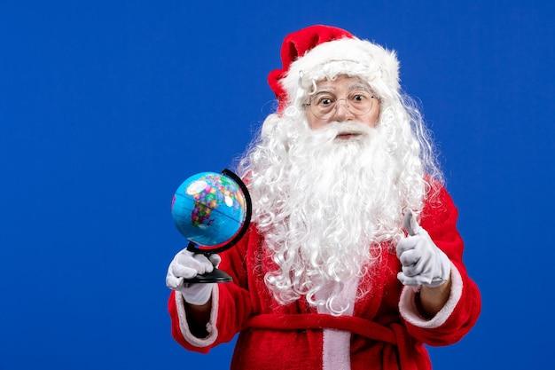 Vue de face du père noël tenant un petit globe terrestre sur les vacances de noël couleur bleu nouvel an