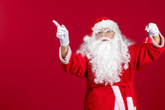 Vue de face du père noël tenant une petite cloche sur un cadeau rouge émotion noël vacances du nouvel an