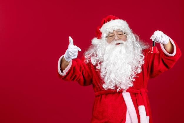 Vue de face du père noël tenant une petite cloche sur un cadeau rouge émotion noël vacances nouvel an