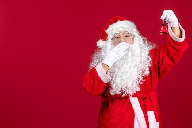 Vue de face du père noël tenant une petite cloche sur un cadeau rouge émotion vacances de noël nouvel an