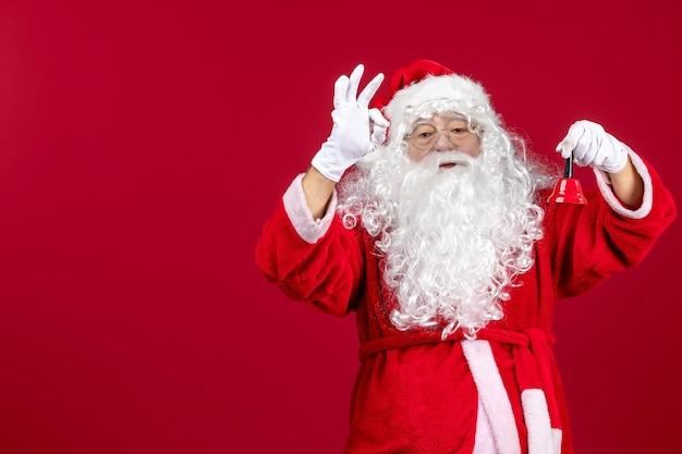 Vue de face du père noël tenant une petite cloche sur un cadeau rouge émotions noël vacances nouvel an