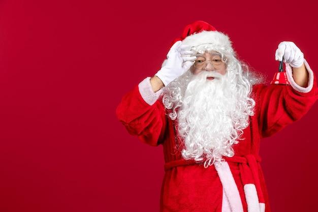 Vue de face du père noël tenant une petite cloche sur un cadeau rouge vacances de noël émotion du nouvel an