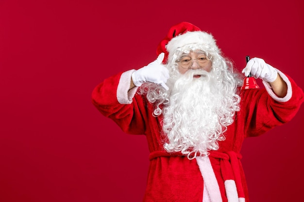 Vue de face du père noël tenant une petite cloche sur les cadeaux du nouvel an de noël rouge vacances d'émotion
