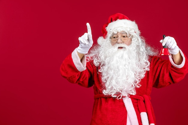 Vue de face du père noël tenant une petite cloche sur le sol rouge vacances d'émotion de noël nouvel an