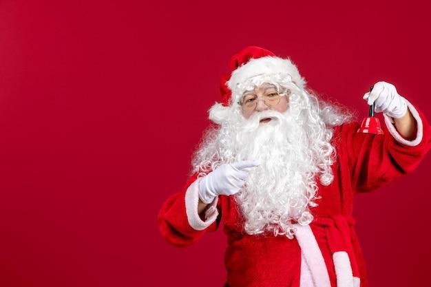 Vue de face du père noël tenant une petite cloche sur les vacances de cadeau du nouvel an de noël émotion rouge