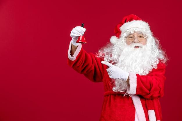 Vue de face du père noël tenant une petite cloche sur les vacances d'émotion du nouvel an de noël rouge