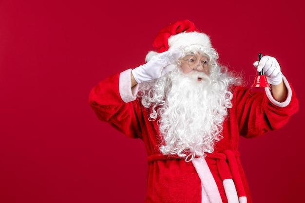 Vue de face du père noël tenant une petite cloche sur les vacances d'émotions du nouvel an de noël rouge