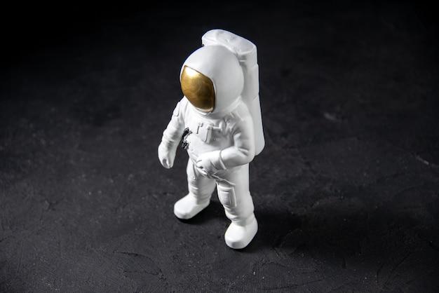 Vue de face du petit jouet spaceman sur le noir