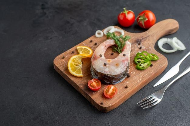 Vue de face du poisson cru et des légumes frais hachés tranches de citron épices sur une planche de bois sur le côté gauche sur une surface noire en détresse