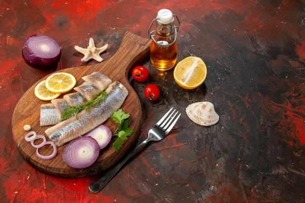 Vue de face du poisson cru en tranches avec des rondelles d'oignon sur de la viande de salade de couleur sombre aux fruits de mer