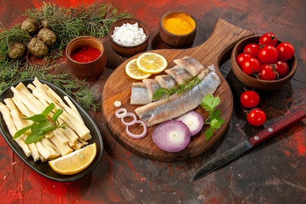 Vue de face du poisson frais tranché avec assaisonnements tomates et fromage sur des fruits de mer foncés photo couleur collation viande salade mûre
