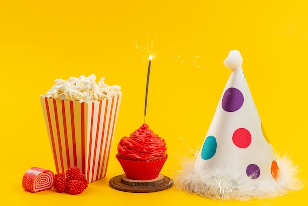 Une vue de face du pop-corn et du gâteau avec chapeau d'anniversaire et marmelades sur bureau jaune