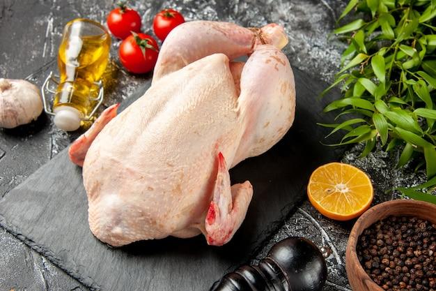 Vue de face du poulet cru frais avec des tomates sur le repas de cuisine clair-foncé photo d'animal couleur de viande de poulet nourriture de ferme
