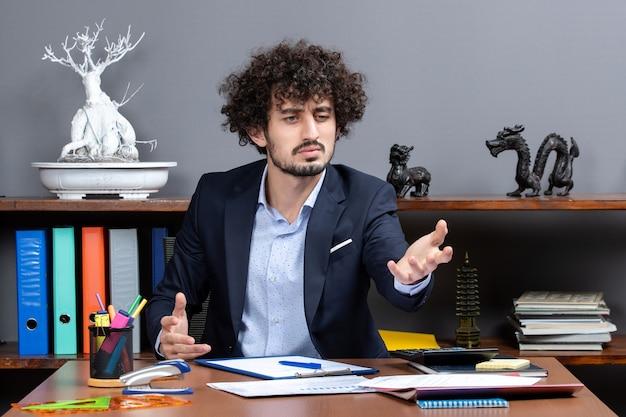Vue de face du processus de travail confus employé de bureau en tenue de soirée assis au bureau