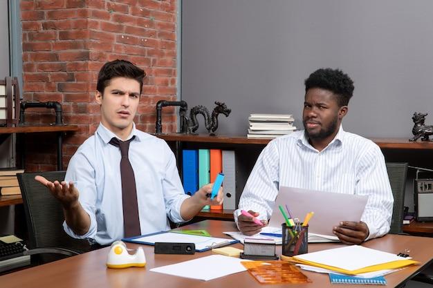 Vue de face du processus de travail de deux hommes d'affaires discutant assis au bureau dans un bureau moderne